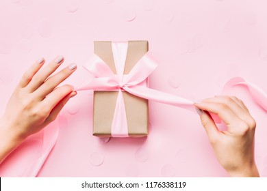 Beautiful woman hands with beautiful pastel manicure open gift box on pink trendy background. Holiday gift and trendy manicure concept.