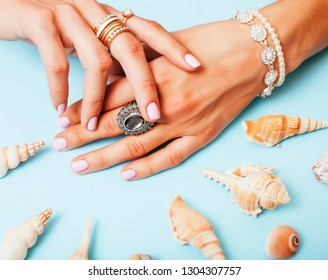 beautiful woman hands with pink manicure with pearls and sea shells, luxury jewelry concept close up
