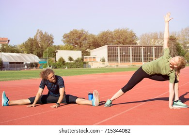 Beautiful woman and a handsome man stretching on the running track and feeling happy. Early morning workout. Living a healthy lifestyle.