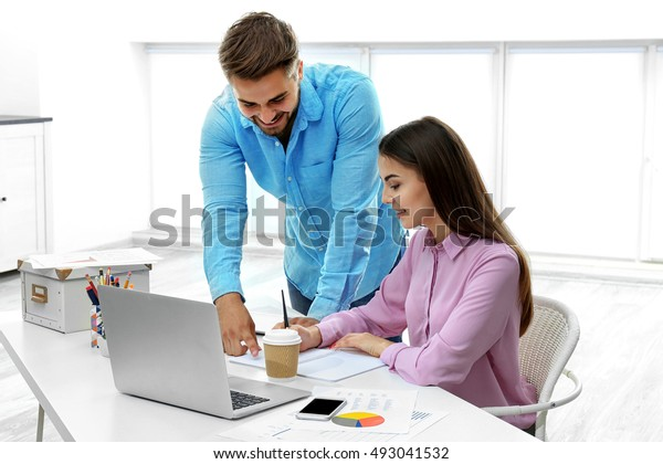 Beautiful woman and handsome man working in modern office