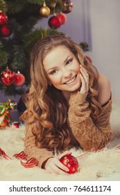 Beautiful woman hanging toy on Christmas tree