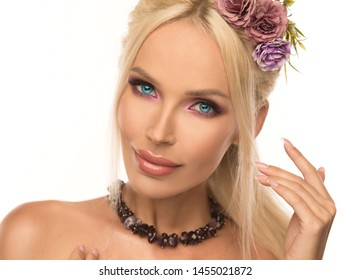 Beautiful woman, has blue eyes, pink make up, blonde hair, sexy big lips, decorated flowers and jewelry bijouterie. White isolated background. Facial plastic botox  surgery.  Summer fashion.