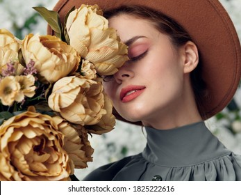 Beautiful woman hat attractive look cosmetics bouquet flowers closed eyes