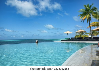 Beautiful woman in hat relaxing in hotel swimming pool. Tropical paradise.