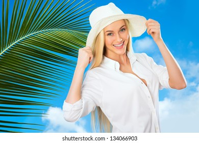 Beautiful woman with hat smiling on a background of tropical landscape