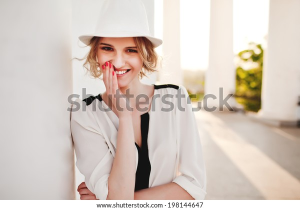 Beautiful woman in hat smiling on  the street in soft sunlight