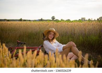 Beautiful woman in hat in summer field