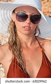 beautiful woman in a hat and sunglasses on the beach in a bikini