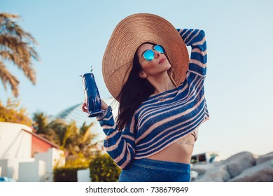 Beautiful woman in a hat and sunglasses on a beach.