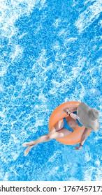 Hermosa mujer en sombrero en la piscina vista aérea superior desde arriba, muchacha joven en relajación bikini y baño en anillo inflable donut y se divierte en el agua en vacaciones familiares, vacaciones tropicales