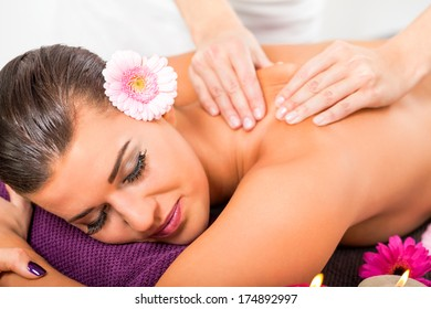 Beautiful woman having a back massage smiling in pleasure as the masseuse at the spa manipulates her shoulder muscles for complete relaxation, burning candles in the foreground