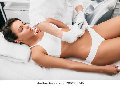 Beautiful woman having cavitation, procedure removing cellulite on her belly at beauty clinic