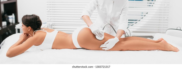Beautiful woman having cavitation, procedure removing cellulite on legs and buttocks at beauty clinic