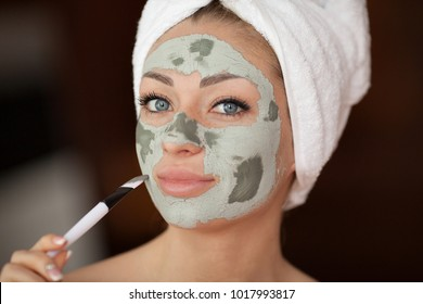 Beautiful woman having clay facial mask apply by beautician.