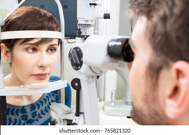 Beautiful woman having an eye exam with slit lamp / Ophthalmologist in eyes clinic doing an exam diagnostic with vision of patient by modern computer systems - high technology concept and eyes care