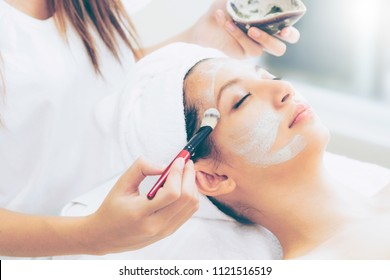 Beautiful woman having a facial cosmetic scrub treatment from professional dermatologist at wellness spa. Anti-aging, facial skin care and luxury lifestyle concept.