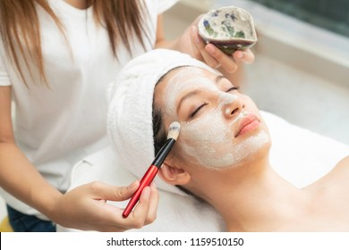 Beautiful woman having a facial mask from dermatologist at spa. Facial mask often contains minerals, vitamins, and fruit extracts. The effect of facial mask can be revitalizing or rejuvenating.