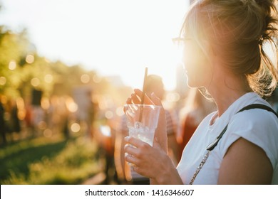 Beautiful woman having fun on a party in summer day. Female drinking iced cocktail at festival.