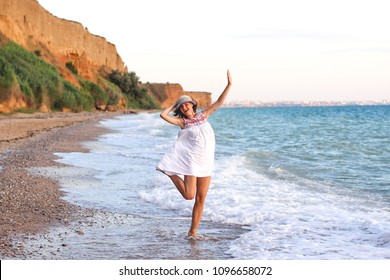 Beautiful woman having fun walking on the beach at sunset. Family, vacation concept.