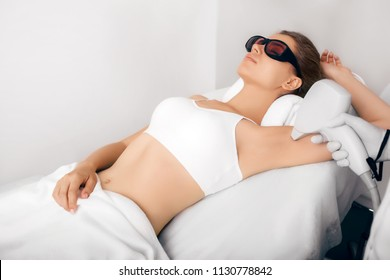Beautiful woman having her armpit hair removed by female beautician. Lazer epilation treatment, at clinic