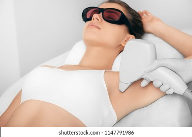 Beautiful woman having her armpit hair removed by female beautician. Lazer epilation treatment, at clinic, selective focus armpit
