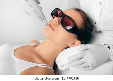 Beautiful woman having her facial hair removed by female beautician. Lazer epilation treatment, at clinic