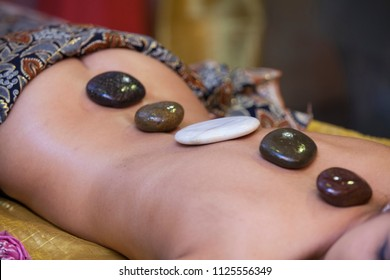 Beautiful woman having hot stones on her back in spa salon. concept of healthcare and female beauty. view of the woman's back with hot stones from the front