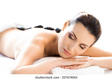 Beautiful woman having hot stones on her back in spa salon.