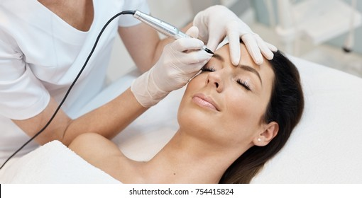 Beautiful woman having professional eyebrow tattoo in beauty salon.