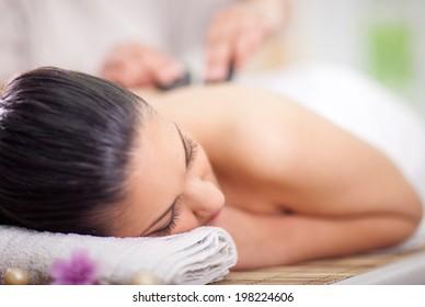 Beautiful woman having a wellness back massage at spa salon