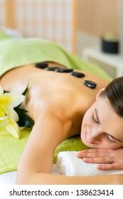 Beautiful woman having a wellness hot stone back massage