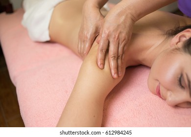Beautiful woman having a wellness shoulder massage and feeling visibly good about it