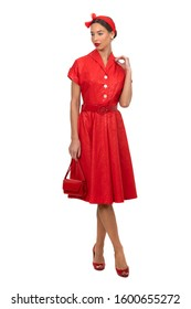 beautiful woman with a headband in a stylish red vintage dress posing on a white studio background