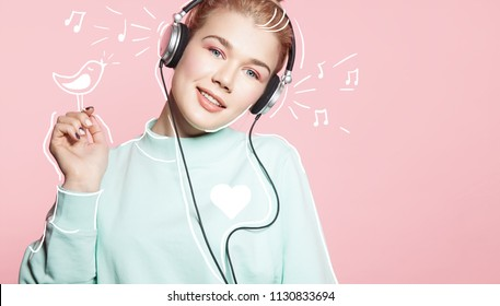 Beautiful woman in headphones listening to music smiling with closed eyes standing on a pink background in a blue sweatshirt