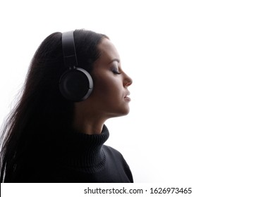 Beautiful woman in headphones listening music with closed eyes. White background. Free space for text.