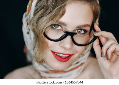 Beautiful Woman Headscarf and Glasses Portrait. Fashion Woman with Makeup Wear Kerchief and Spectacles. Glamour Girl with Red Lip and Green Eye Smiling. Bronze Shiny Make-up Front View Shoot