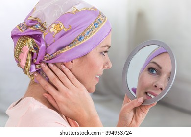 Beautiful woman with a headscarf looking  on mirror