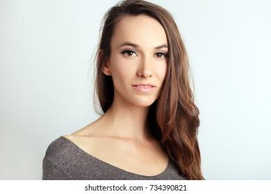 beautiful woman headshot near the wall, light grey background