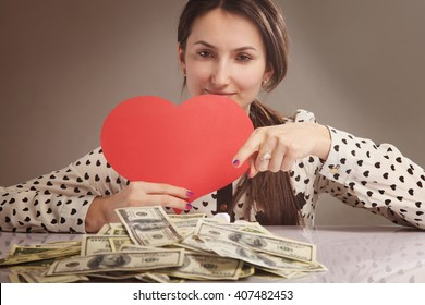 beautiful woman with heart in the hands as symbol love of money