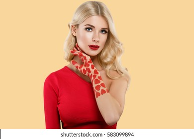 Beautiful woman hearts art red lips face close up portrait young studio on yellow