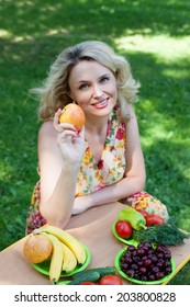 Beautiful woman in her 30s holding apple and smiling, on background of fruits and vegetables in garden park outdoors