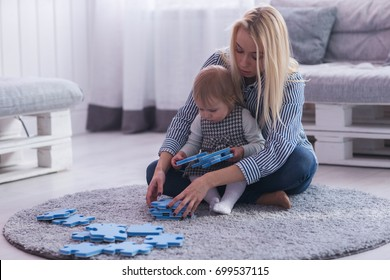 Beautiful woman and her baby playing with puzzle pieces