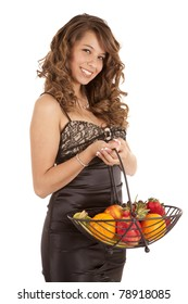 a beautiful woman in her black formal dress, with a smile on her face, holding a bowl of fruit.