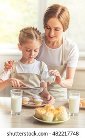 Beautiful woman and her cute little daughter in aprons are smiling while dusting muffins with sugar powder