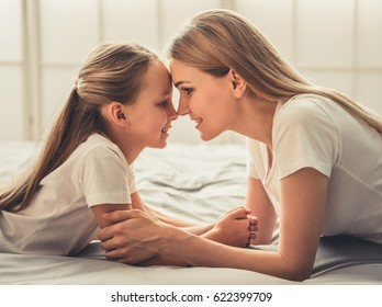 Beautiful woman and her cute little daughter are touching noses and smiling while lying on bed