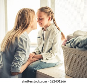 Beautiful woman and her cute little daughter are touching their noses and smiling while doing laundry at home
