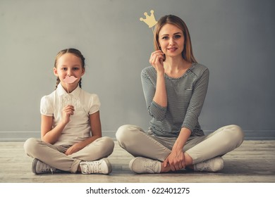 Beautiful woman and her cute little daughter are holding paper crown and lips, looking at camera and smiling while sitting on the floor