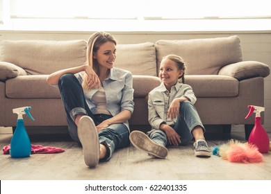Beautiful woman and her cute little daughter are sitting on the floor, looking at each other and smiling after cleaning their house