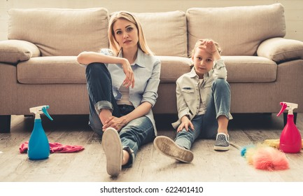Beautiful woman and her cute little daughter are sitting tired on the floor and looking at camera after cleaning their house