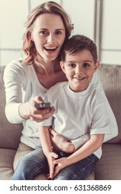 Beautiful woman and her cute little son are watching TV, looking at camera and smiling while sitting on sofa at home
